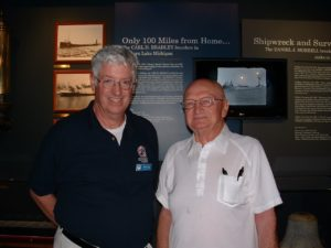 Development Officer Sean Ley with Bradley survivor Franks Mays in front of the Bradley exhibit in Shipwreck Museum