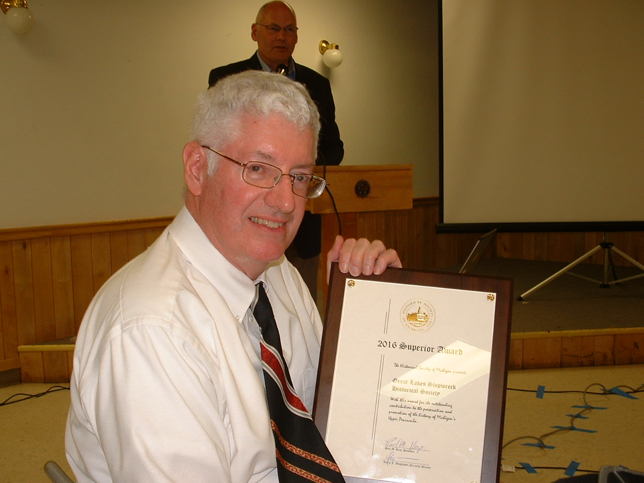 Sean Ley, Shipwreck Society Development Officer, holds the Superior Award, with HSM President Paul Keep in background.